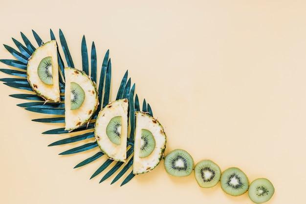 Tranches de fruits sur feuilles de palmier