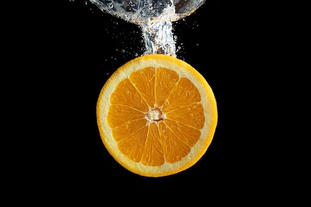 Tranches de fruits orange frais dans les éclaboussures d'eau isolé sur fond noir.