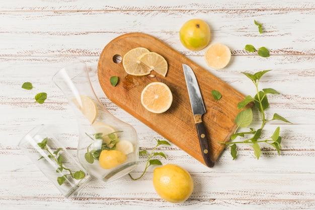 Tranches de fruits près du couteau sur une planche à découper entre des herbes et des verres