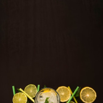 Tranches de fruits près d'un verre avec de la glace