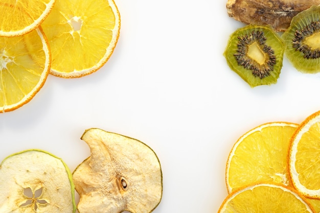 Tranches de fruits secs de pommes kiwi orange sur fond blanc espace pour le texte