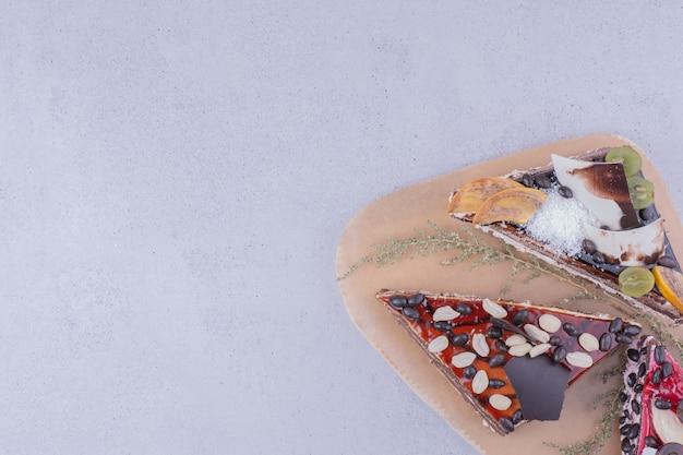 Tranches de gâteau au caramel, chocolat et noix sur un plateau en bois.