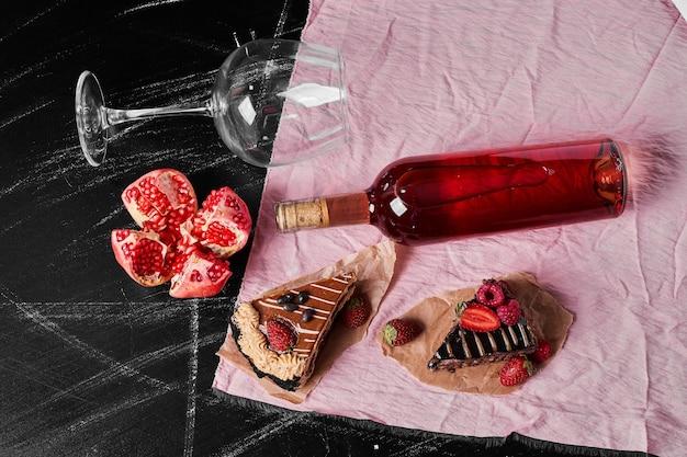 Tranches de gâteau au chocolat avec du vin sur fond noir