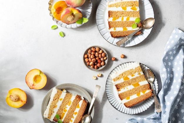 Tranches de gâteau aux pêches avec crème au beurre et miel sur fond clair