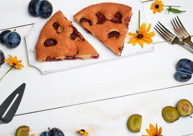 Tranches de gâteau aux prunes biscuit sur une planche en bois blanche et fruits frais