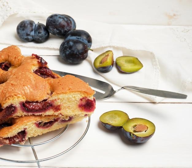 Tranches de gâteau aux prunes sur une planche en bois blanche et fruits frais