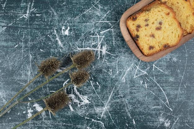 Tranches de gâteau aux raisins secs et plante sur mur de marbre.