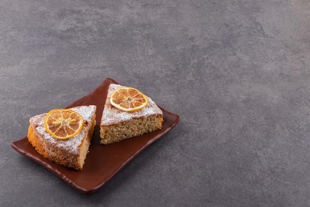 Tranches de gâteau fait maison frais sur une plaque sur une surface grise