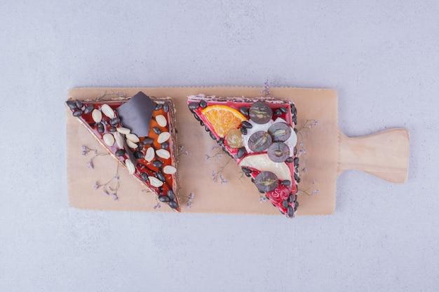 Tranches de gâteau en forme de triangle avec du chocolat, des noix et des fruits sur un plateau en bois