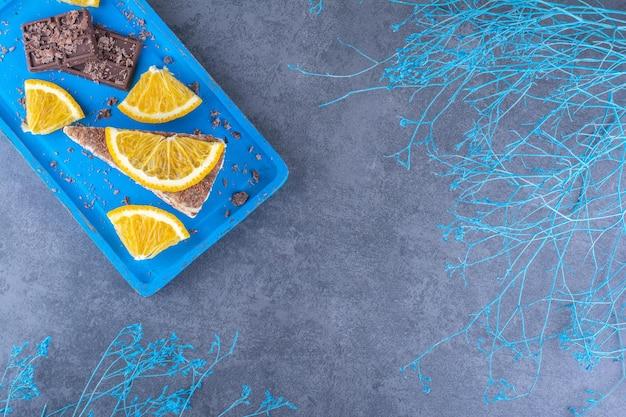 Tranches de gâteau et d'orange avec des plaques de chocolat sur un plateau à côté de branches décoratives sur la surface en marbre