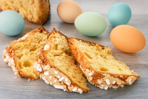 Des tranches de gâteau de pâques et des œufs colorés sont sur une table en bois.