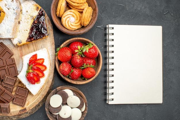 Tranches de gâteau vue de dessus avec des biscuits aux fruits et des barres de chocolat sur une surface sombre