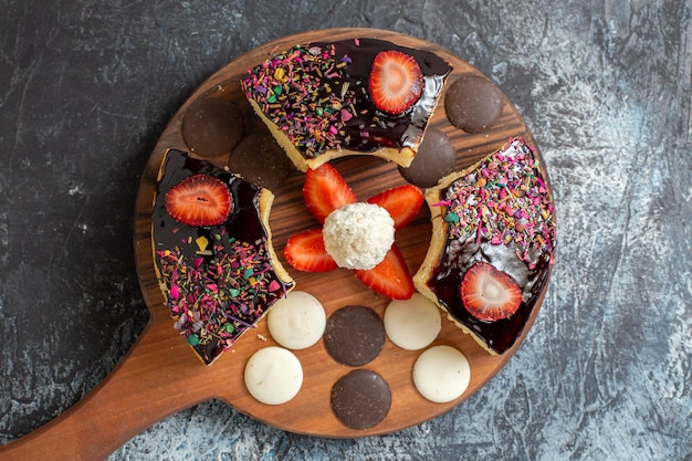 Tranches de gâteau vue de dessus avec des biscuits sur une surface sombre et claire