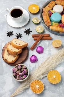 Tranches de gâteau vue de dessus avec des bonbons et une tasse de thé sur blanc