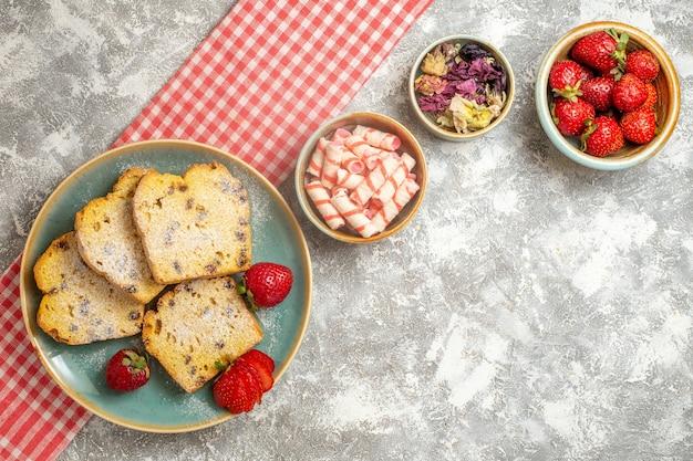 Tranches de gâteau vue de dessus avec des fraises fraîches sur des fruits de tarte sucrée de surface légère