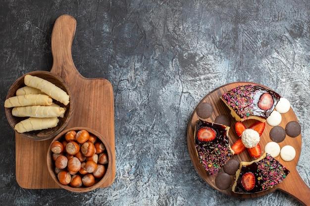 Tranches de gâteau vue de dessus avec des noix et des bonbons sur une surface sombre