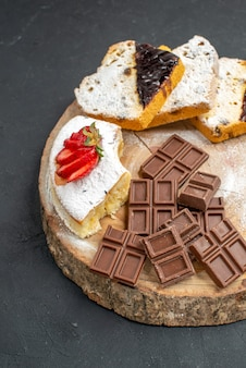 Tranches de gâteau vue de face avec des barres de chocolat sur fond sombre