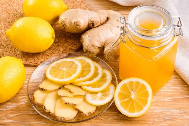 Tranches de gingembre et citron sur une assiette et un pot de miel sur une table en bois