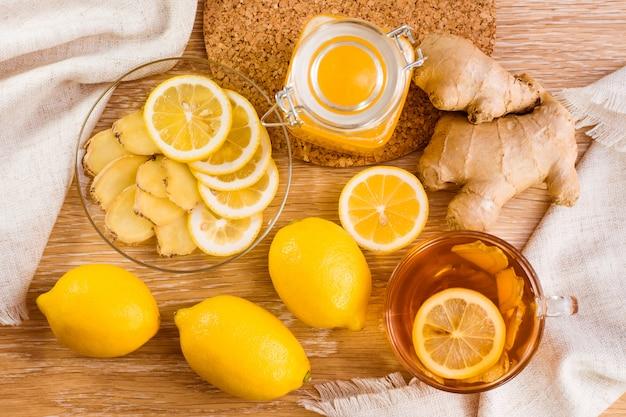 Tranches de gingembre et de citron sur une assiette, pot de miel et tasse de thé au citron sur une table en bois