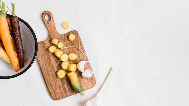 Tranches de gousses d'ail et de carottes sur une planche à découper sur fond blanc