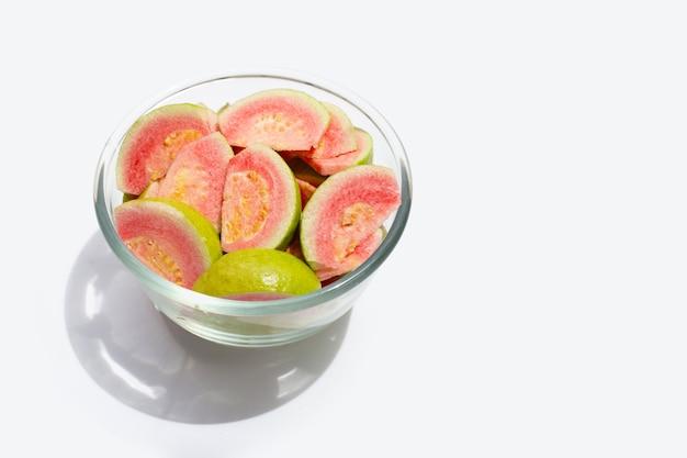 Tranches de goyave rose fraîche sur bol en verre sur fond blanc.