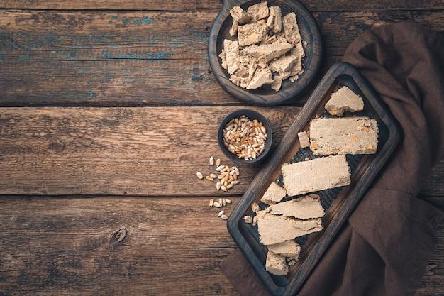 Tranches de halva sur les planches et les graines sur un fond brun. fond culinaire avec espace pour copier.