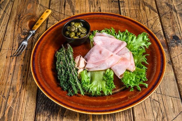 Tranches de jambon fumé avec salade fraîche et câpres sur une assiette sur une table en bois. vue de dessus.