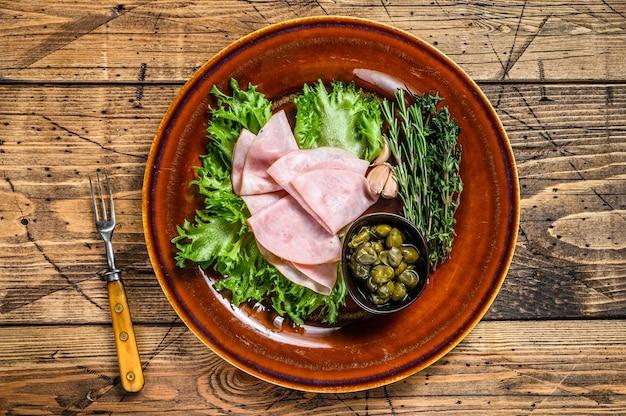 Tranches de jambon fumé avec salade fraîche et câpres sur une assiette