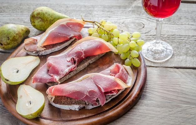 Tranches de jambon italien sur la planche de bois
