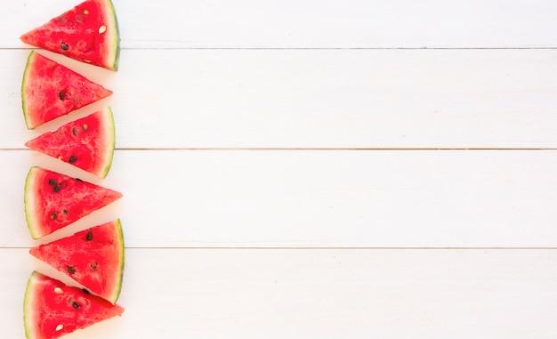 Tranches juteuses de pastèque sur fond de planches de bois blanc
