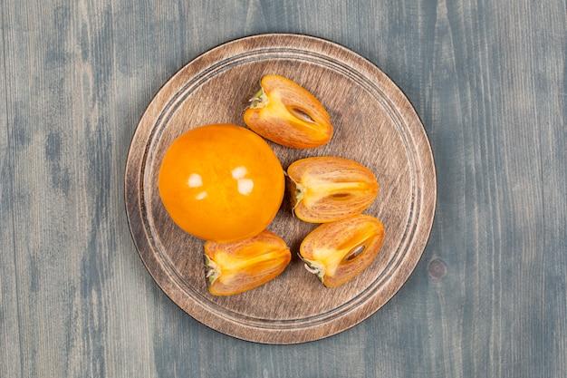 Tranches de kaki délicieux dans une assiette en bois