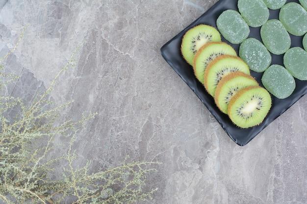 Tranches de kiwi et bonbons à la marmelade sur plaque noire.