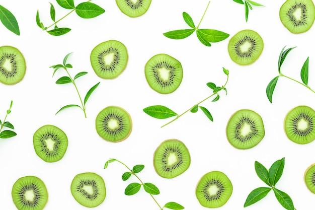 Tranches de kiwi et de feuilles vertes sur la surface grise
