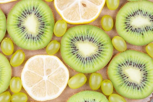 Tranches de kiwi frais, de raisins et de citron sur une planche à découper en bois.