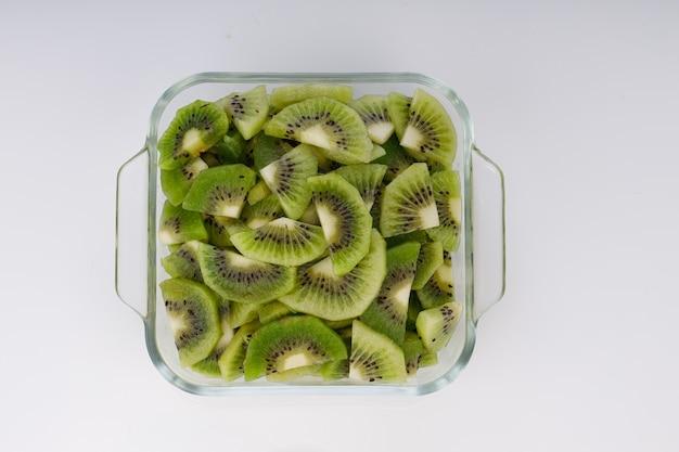 Tranches de kiwi ou morceau coupé disposés dans un récipient carré en verre avec un fond de couleur blanche.