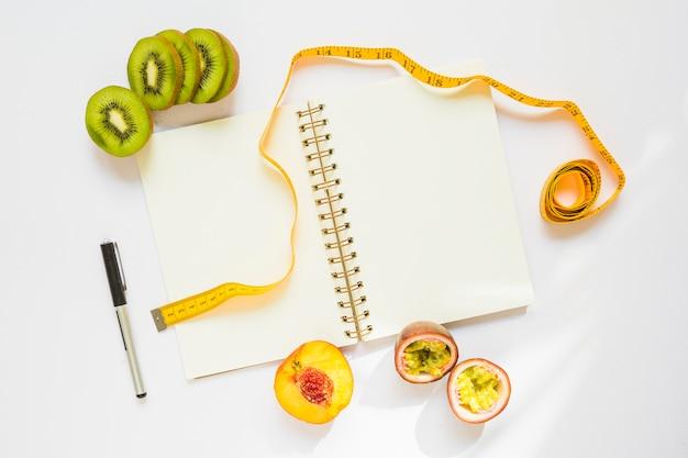 Tranches de kiwi; pêche et fruits de la passion avec ruban à mesurer; stylo et cahier à spirale sur fond blanc