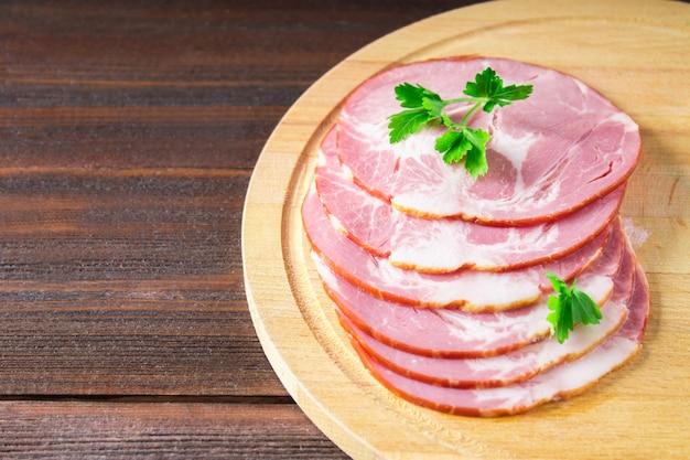 Tranches de laitue verte fraîche de jambon sur une planche à découper ronde.