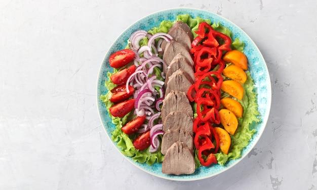 Tranches de langue de porc avec des légumes sur une plaque bleue sur une surface grise. excellent apéritif froid. vue de dessus. espace pour le texte.