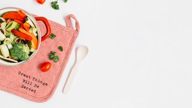 Tranches de légumes dans une marmite sur napperon avec texte