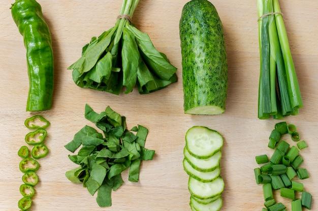 Tranches de légumes verts sur une planche à découper. pose à plat