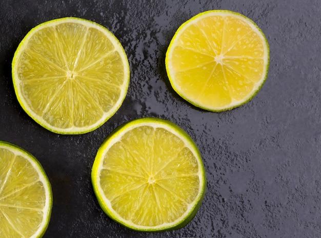 Tranches de lima fraîches avec des gouttes d'eau sur fond noir