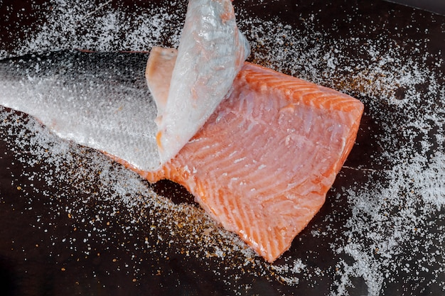 Des tranches de main féminine de saumon cru survivent à un morceau de saumon cru, d'épices, à un fond sombre.