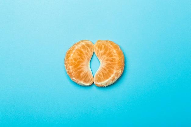 Tranches de mandarine sur un fond minimal de couleur vierge. métaphore de la vulve féminine. concept de créativité et d'idée.