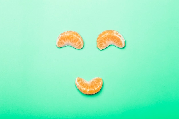 Tranches de mandarine sur un fond minimal de couleur vierge. visage drôle fait de tranches de mandarine. concept de créativité et d'idée.