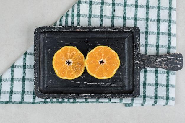 Tranches de mandarine fraîche sur tableau noir