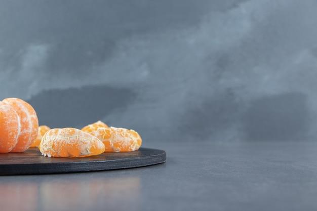Tranches de mandarine savoureuses sur une planche à découper.