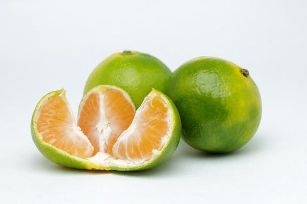 Tranches de mandarine sur une surface blanche
