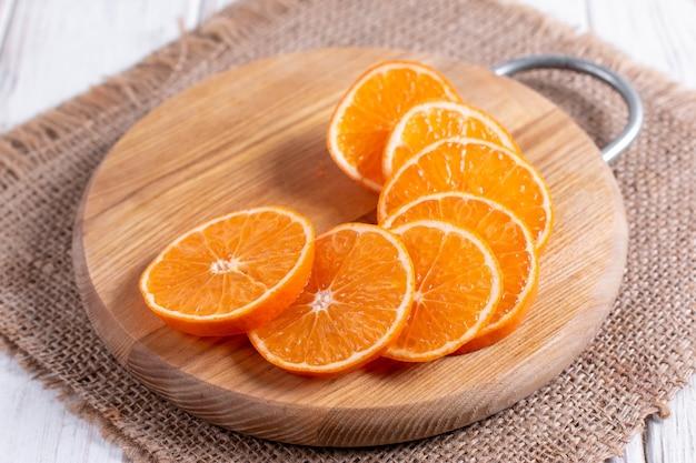 Tranches de mandarines mûres juteuses sur une planche à découper en bois