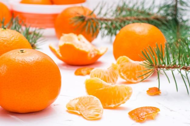 Tranches de mandarines purifiées, mandarines entières et branches de sapin sur une table blanche