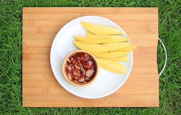 Tranches de mangue aigre avec sauce de poisson sucrée dans une assiette blanche sur une planche en bois de bambou sur fond d'herbe verte. vue de dessus